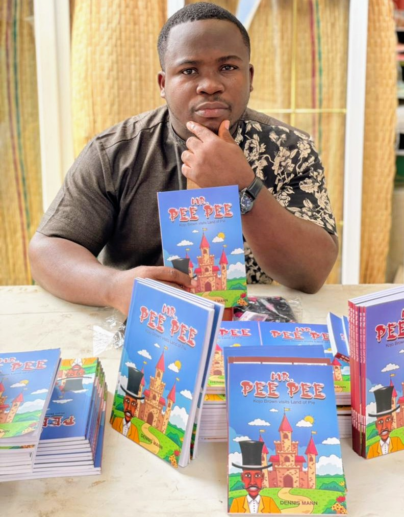 Young Black man sitting at a table in front of a pile of Mr. Pee Pee books.