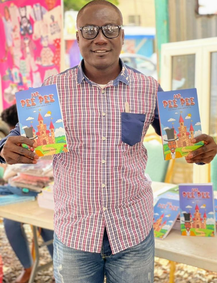 Young Black man with glasses and a plaid top and jeans holding some Mr. Pee Pee books.