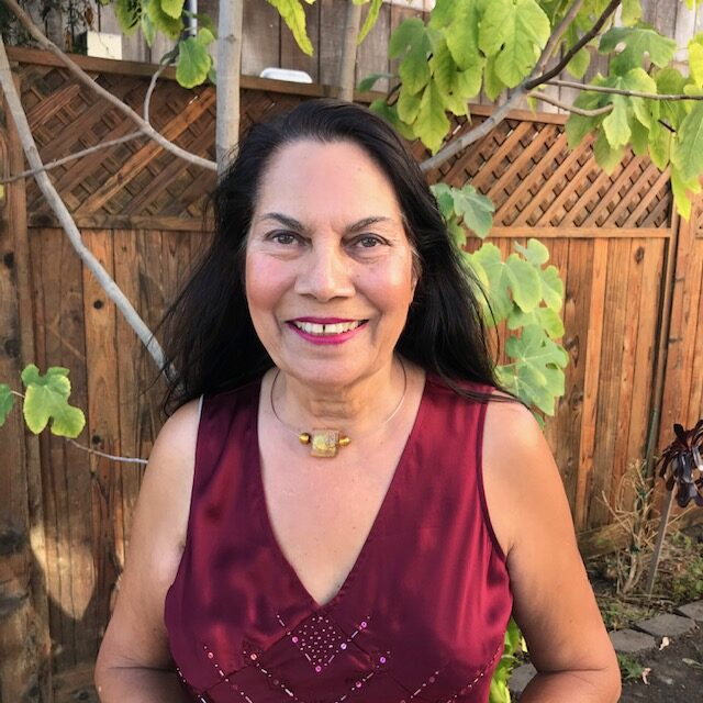 Middle aged South Asian woman with a large shiny golden necklace and a burgundy top standing in front of a fig tree and a fence in a yard.