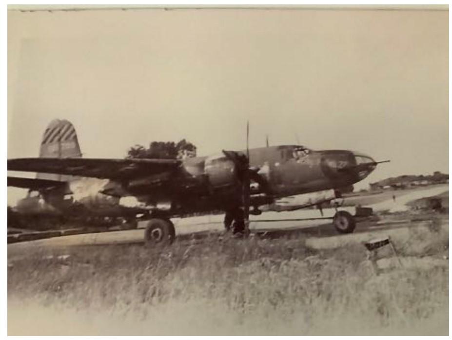 B-26 plane taking off in a field.