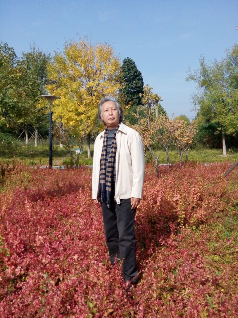 Older Chinese man with a white coat and scarf and black jeans standing in a field with a reddish-brown leaved shrub behind him and a yellow tree and some green trees and a lamp behind him.