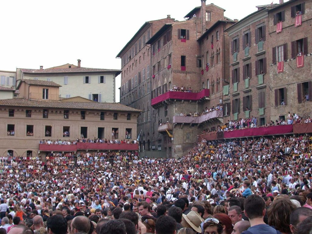 Lots of people in Siena in front of old buildings getting ready to watch the palio!
