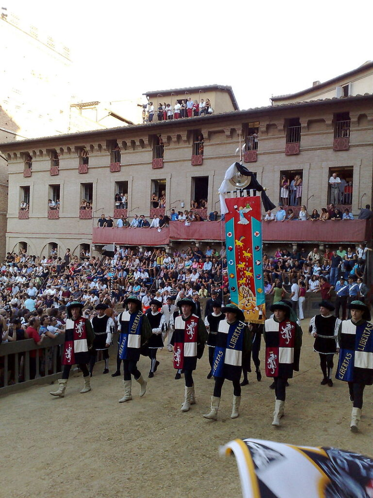 Parade with men in traditional colorful costume and a banner