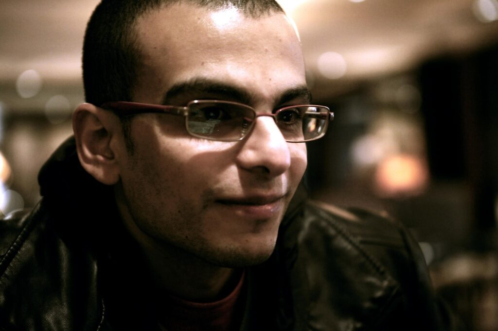 Egyptian man with glasses and a black or brown jacket in half-light.