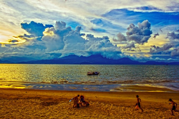 Beach at sunset or sunrise, gauzy yellow light over sand and blue water and sky. Children play on the sand with pails.